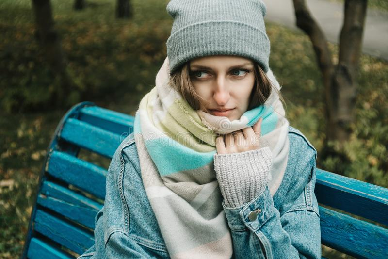 Lifestyle autumn portrait of young adult woman sitting on a bench royalty free stock photos
