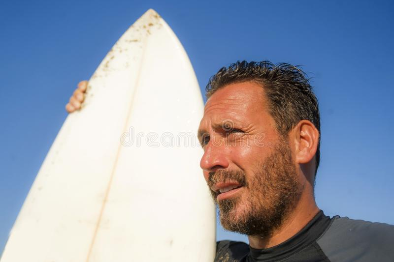 Handsome and attractive surfer man in neoprene swimsuit holding surf board posing cool after surfing enjoying Summer water sport stock images