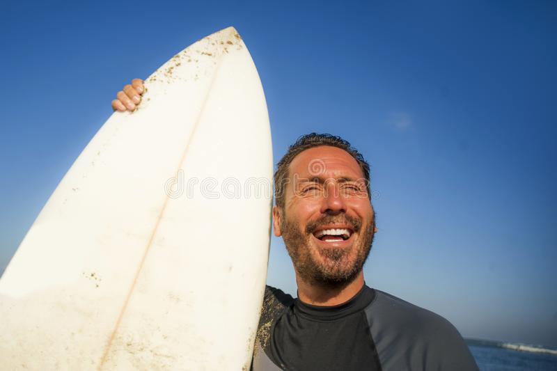 Handsome and attractive surfer man in neoprene swimsuit holding surf board posing cool after surfing enjoying Summer water sport royalty free stock photo
