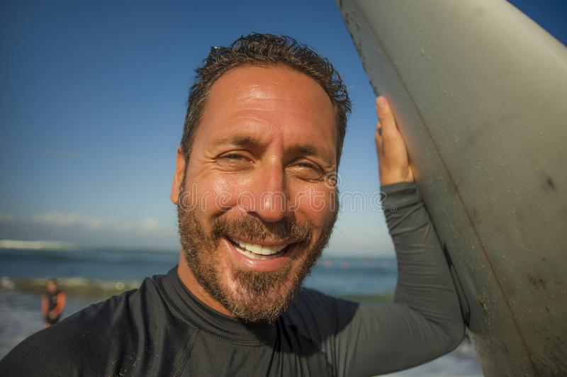 Lifestyle beach closeup portrait of handsome and attractive surfer man in neoprene swimsuit holding surf board posing cool after royalty free stock photos