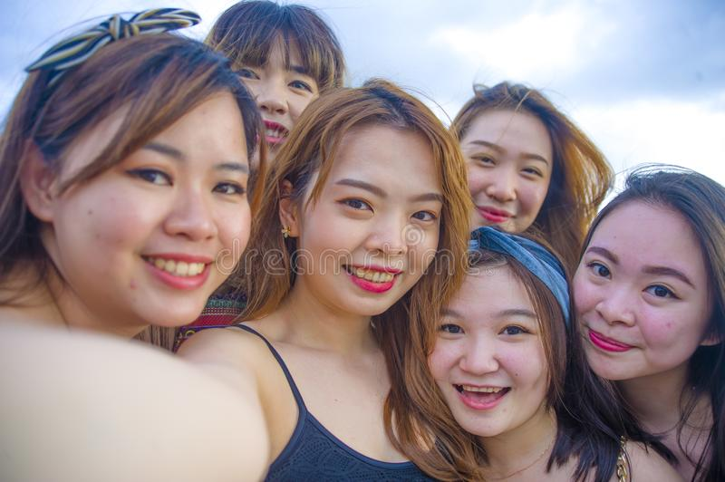 Lifestyle beach portrait of Asian Korean and Chinese women, group of happy beautiful young girlfriends taking selfie picture toget royalty free stock photos