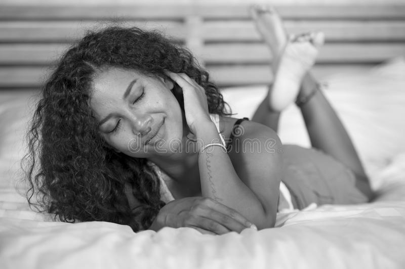 Lifestyle black and white portrait of young happy and gorgeous hispanic woman posing and playful at home bedroom lying relaxe. D on bed in pajamas shorts looking royalty free stock photo