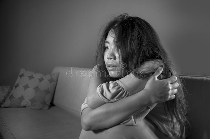 Young sad and depressed Asian Japanese woman at home sofa couch crying desperate and helpless suffering anxiety and depression fee. Lifestyle black and white royalty free stock photography