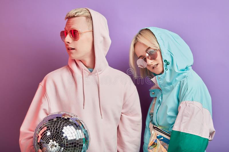 Young fashionable couple of dancers posing with disco ball on violet background royalty free stock photography