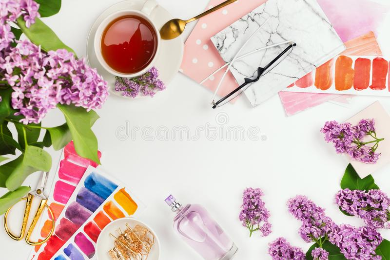 Lifestyle and business mockup flatlay with cup of tea, lilac, notebook, perfume and other accessories royalty free stock images