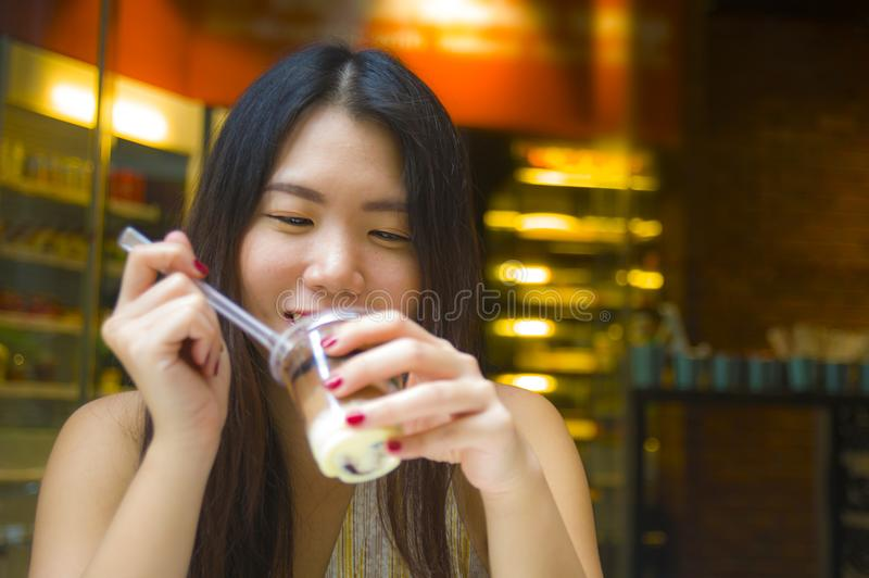 Lifestyle candid portrait of young beautiful and happy Asian Korean woman having breakfast at coffee shop outdoors smiling cheerfu royalty free stock photos