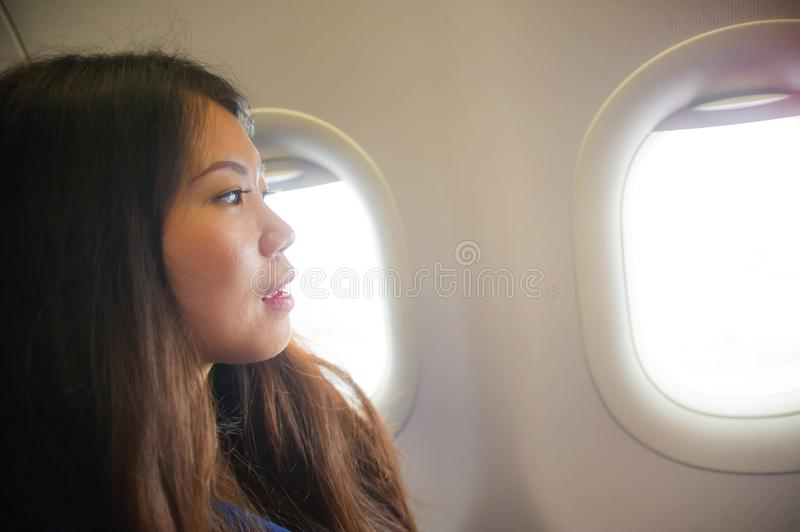 Lifestyle candid portrait of young happy and beautiful Asian Korean woman traveling for holidays inside airplane cabin excited on royalty free stock images
