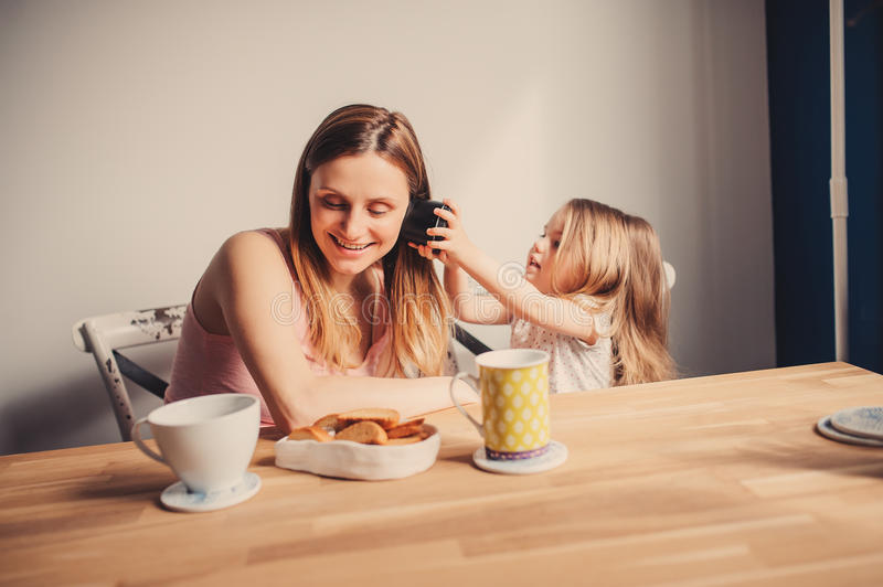 Lifestyle capture of happy mother and baby girl having breakfast at home stock image