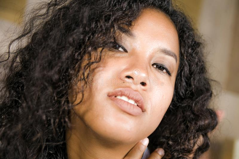 Lifestyle close up head portrait of young beautiful and mixed ethnicity latin and African American woman with gorgeous curly. Hair in seductive face expression royalty free stock photography