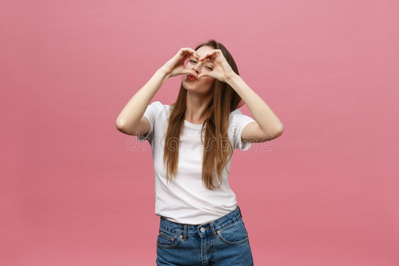 Lifestyle Concept: Beautiful attractive woman in white shirt making a heart symbol with her hands stock photos