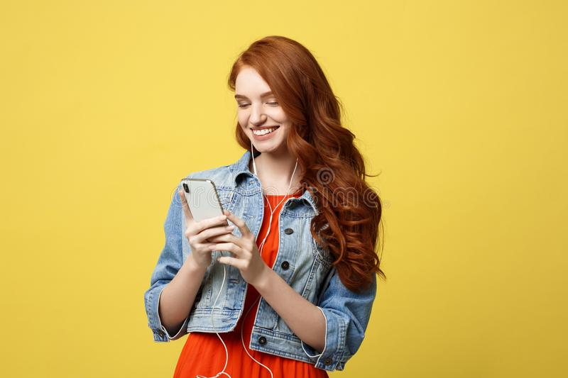 Lifestyle Concept: Beautiful young woman in headphones listening to music on light yellow background stock images