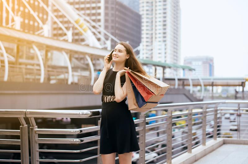 Lifestyle concept,Portrait of beautiful women in black dress using cellphone and holding shopping bags at city,Selective focus royalty free stock photo