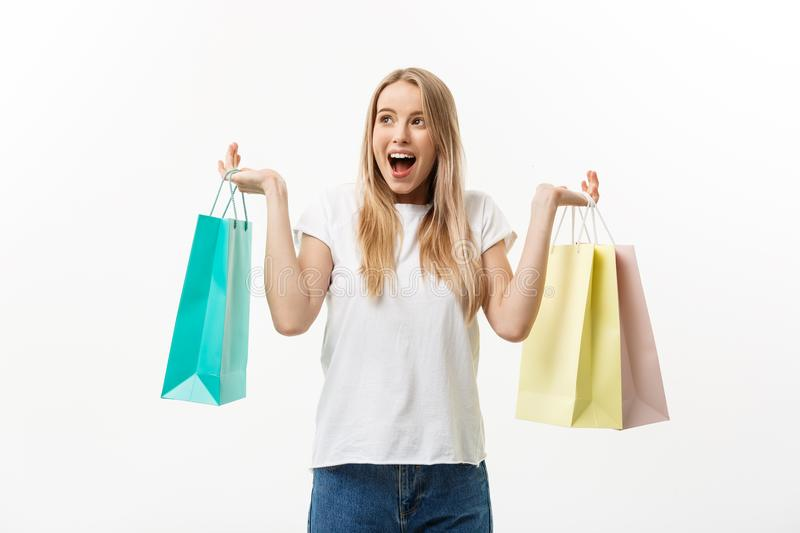 Lifestyle Concept: Portrait shocked young brunette woman in white summer shirt posing with shopping bags isolated over royalty free stock photo