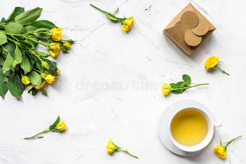 Lifestyle concept with tea and roses on home desk top view mock-up royalty free stock images