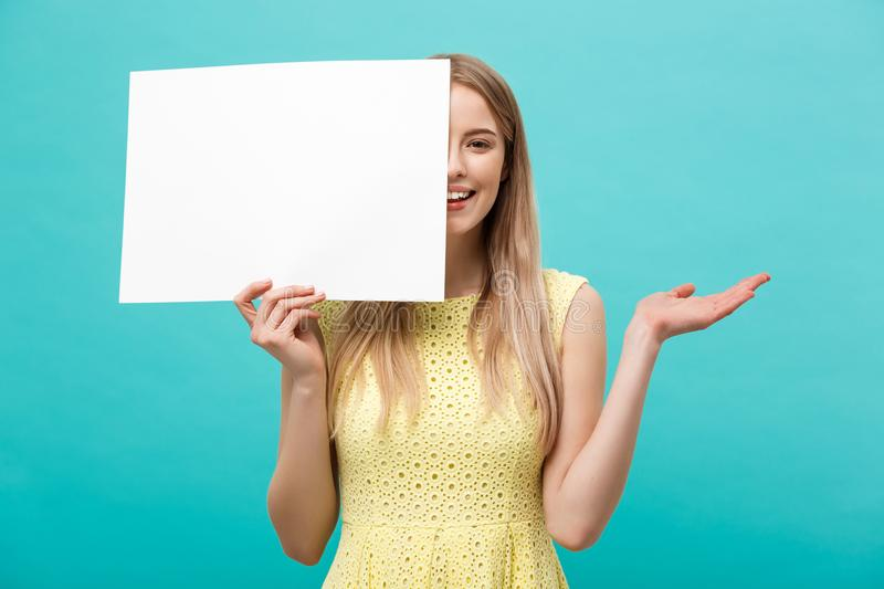 Lifestyle Concept: young beautiful girl smiling and holding a blank sheet of paper, dressed in yellow, isolated on. Pastel blue background royalty free stock photo