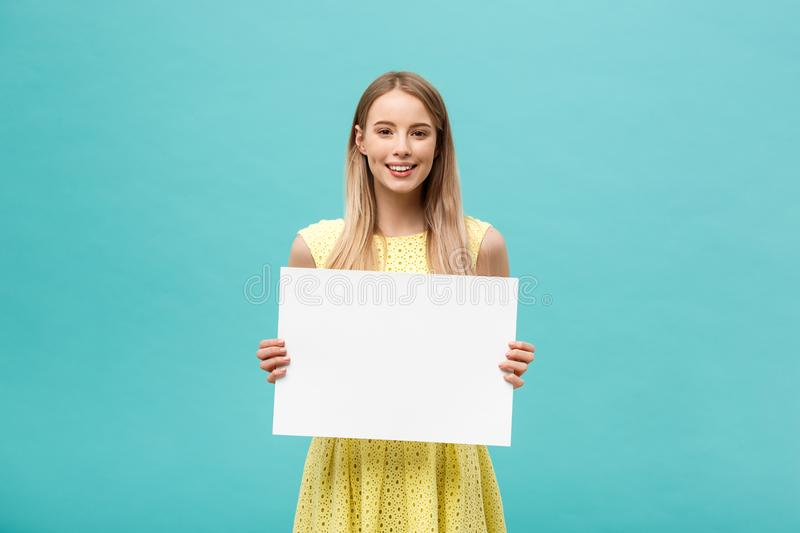 Lifestyle Concept: young beautiful girl smiling and holding a blank sheet of paper, dressed in yellow, isolated on. Pastel blue background stock images