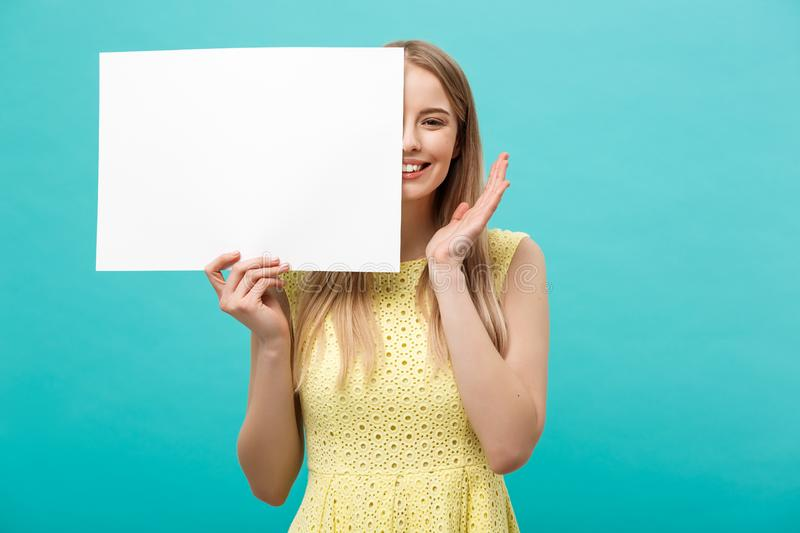Lifestyle Concept: young beautiful girl smiling and holding a blank sheet of paper, dressed in yellow, isolated on. Pastel blue background stock image