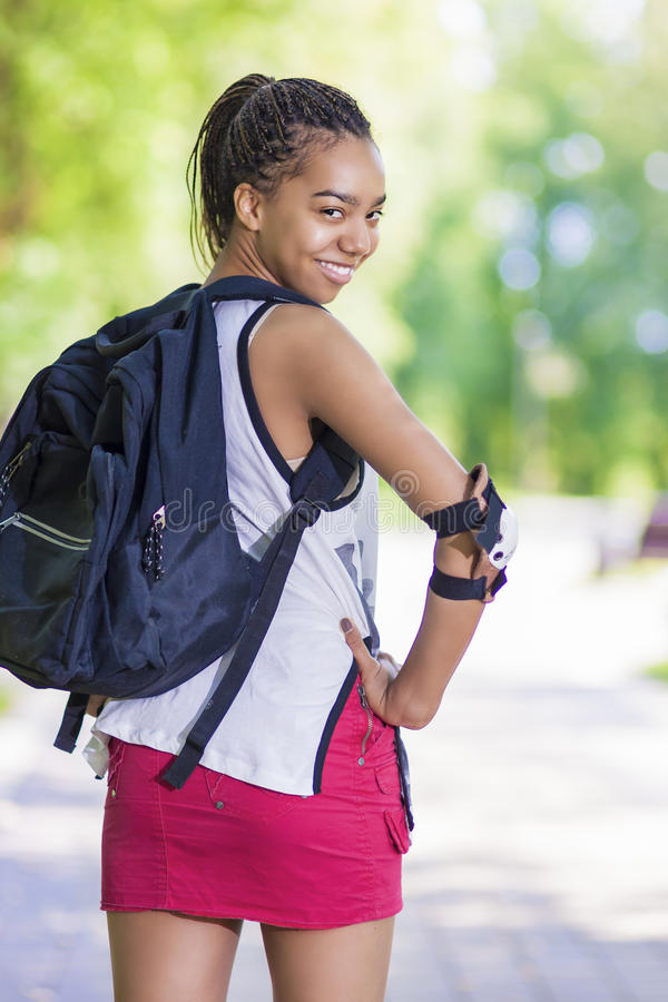 Lifestyle Concepts. Portrait of Happy Positive African American Teenage Girl. Posing Outdoors in Park. Vertical Image Orientation stock photography