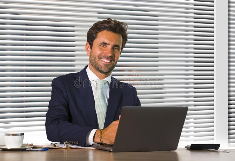 Lifestyle corporate company portrait of young happy and successful business man working relaxed at modern office sitting by window stock photography