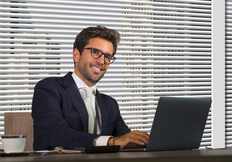 Lifestyle corporate company portrait of young happy and successful business man working relaxed at modern office sitting by window stock photos