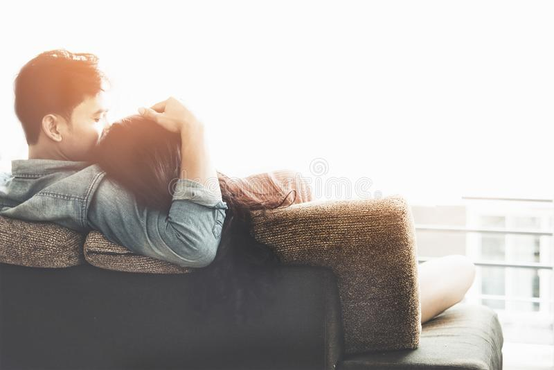 Lifestyle Couple in love and relaxing on a sofa at home and looking outside through the window of the living room, sunny day. royalty free stock photography