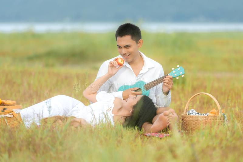 Lifestyle couple picnic sunny time. Asian young couple having fun and relax playing guitar on picnic in the meadow and field in ho royalty free stock photo