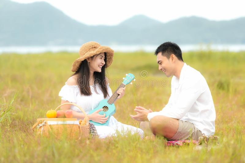 Lifestyle couple picnic sunny time. Asian young couple having fun and relax playing guitar on picnic in the meadow and field in ho royalty free stock image