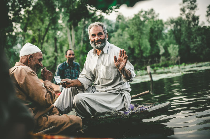 Lifestyle in Dal lake,Kashmiri men sell their vegetables at a floating market in the early hours before sunrise. SRINAGAR,INDIA -JULY 30: Lifestyle in Dal lake royalty free stock image