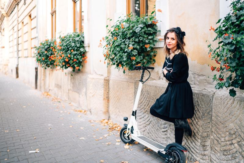lifestyle details - happy woman standing on an alley with flowers and electric kick scooter stock images