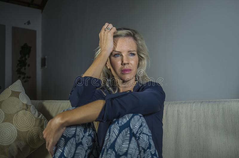 Lifestyle dramatic portrait of attractive and sad woman feeling frustrated and anxious sitting at home sofa couch depressed suffer. Ing anxiety crisis and stock image