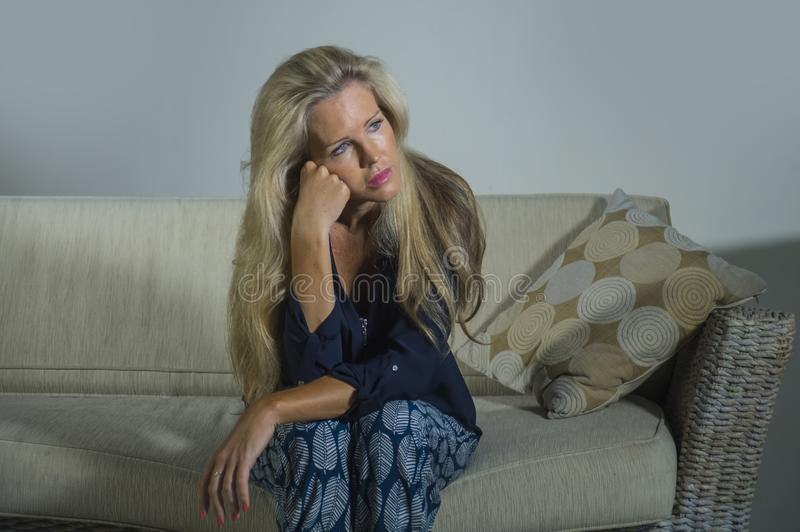 Lifestyle dramatic portrait of attractive and sad woman feeling frustrated and anxious sitting at home sofa couch depressed suffer. Ing anxiety crisis and stock photos