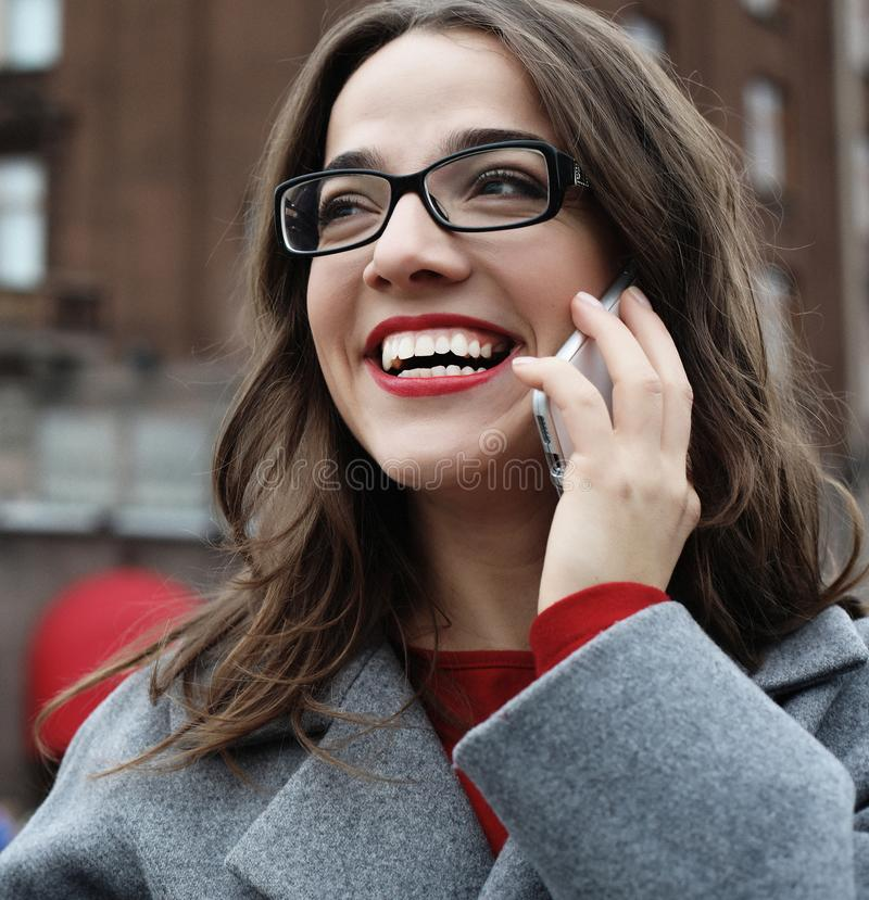 Outdoor portrait of surprised young woman with eyeglasses wearing grey coat and holding smartphone. royalty free stock images