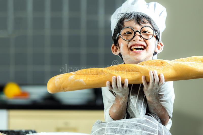 Lifestyle Family. Smiling chef asian kid boy cooking toast and make  bread for dinner.  People children making and leaning sweet f royalty free stock photo