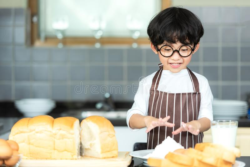 Lifestyle Family. Smiling chef asian kid boy cooking toast and make  bread for dinner.  People children making and leaning sweet f royalty free stock images