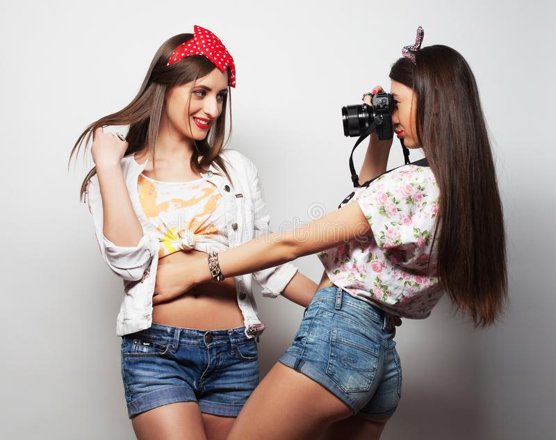 Lifestyle, fashion and people concept: Two young girl friends standing together, take photo and having fun. stock photo