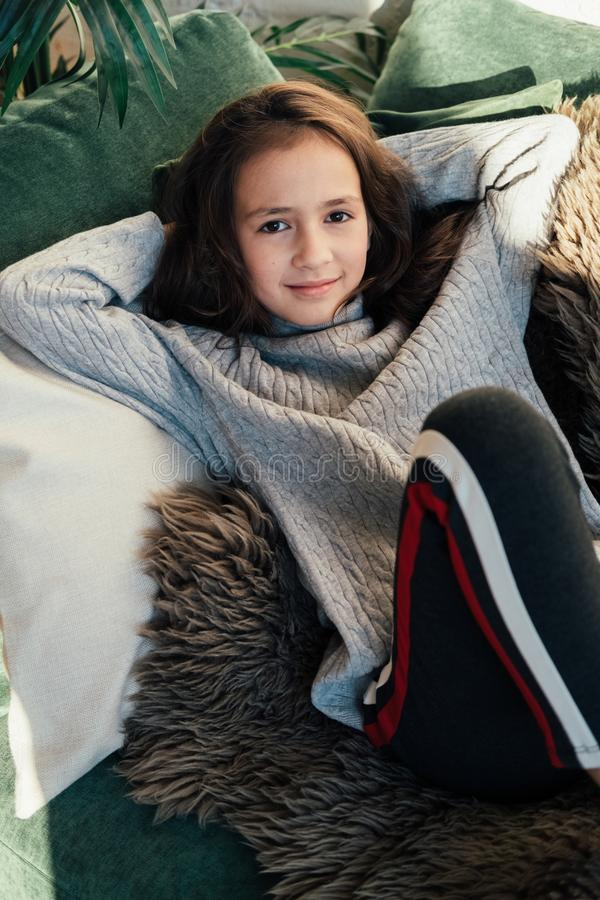 Lifestyle fashion portrait of young stylish hipster child girl sitting near sofa, wearing cute trendy outfit, smiling enjoy weeken royalty free stock image