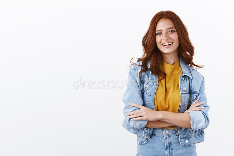 Lifestyle, fashion and women concept. Cheerful ambitious redhead woman in denim jacket cross arms in confident pose royalty free stock photo