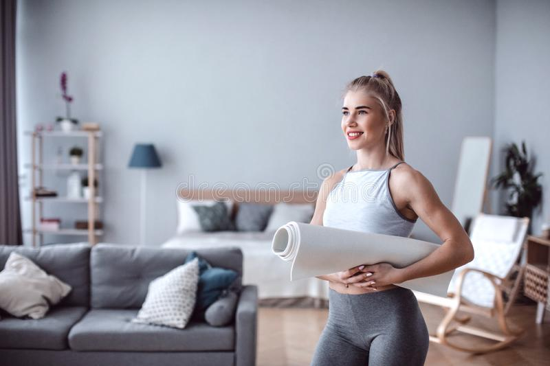 Lifestyle female portrait with yoga mat in living room at home. Yoga or fitness stock photo