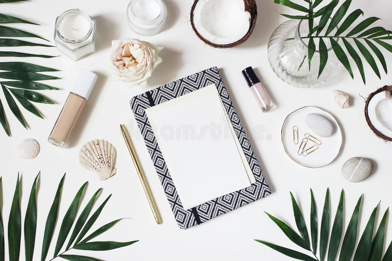Lifestyle feminine desktop composition. Mockup of blank card. Notebook, skin cream, nail varnish and makeup on white. Table background. Frame of coconuts, palm royalty free stock photos