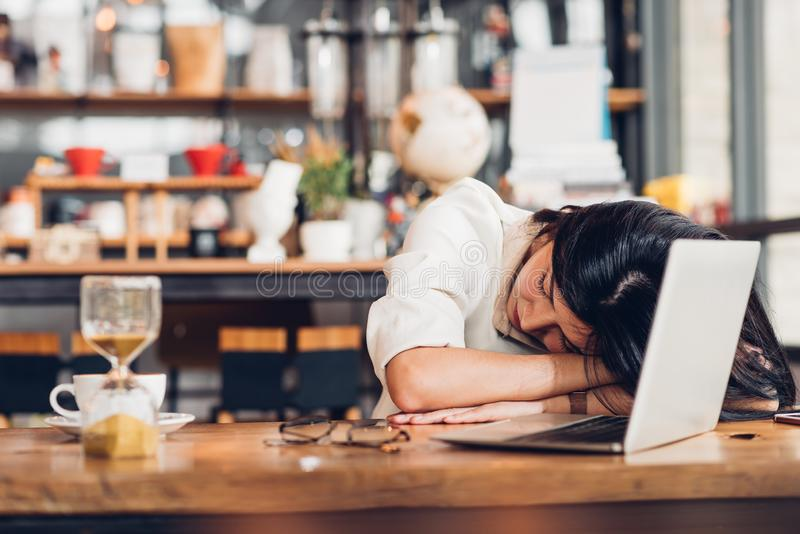 Lifestyle freelance woman he has resting sleeping after hard work long time. In coffee shop royalty free stock photography