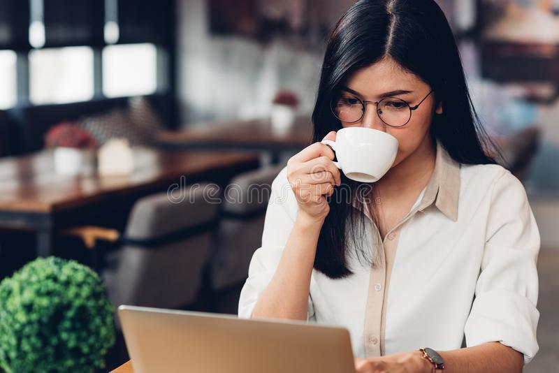 Lifestyle freelance working woman with laptop computer, he drink. Ing coffee in coffee cafe shop royalty free stock image