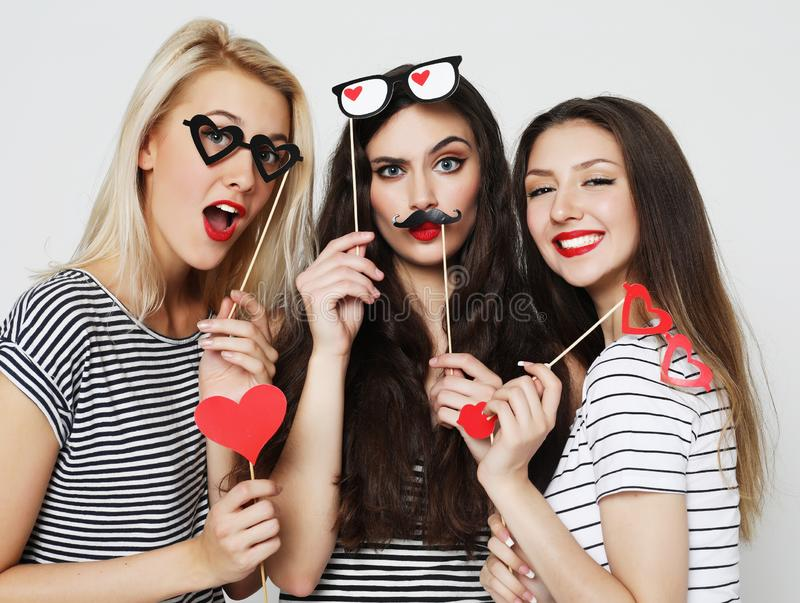 Three young women holding paper party sticks. Lifestyle,friendship and people concept: Three young women holding paper party sticks over white background stock photography
