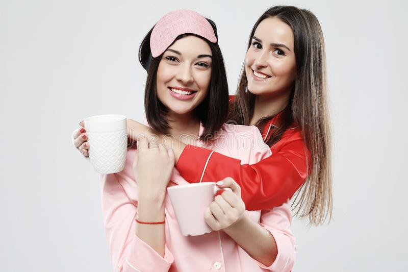 Lifestyle, friendship and people concept - two beautiful girls dressed in pajamas hugging and smiling royalty free stock photo