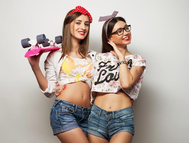 Lifestyle, friendship and people concept: Two young girl friends standing together and having fun. stock photos