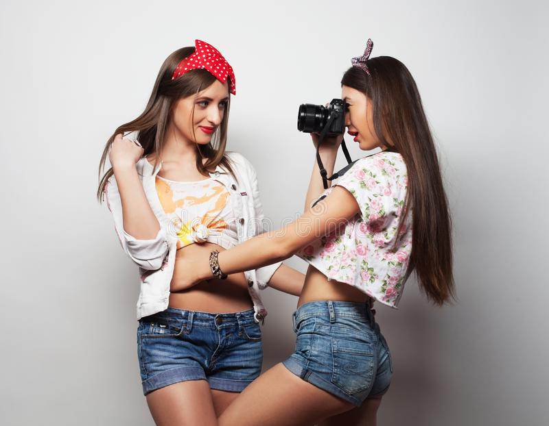 Lifestyle, friendship and people concept: Two young girl friends standing together and having fun. stock photography