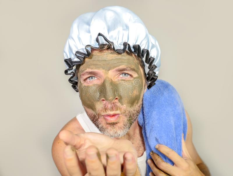 Lifestyle funny portrait of happy weird man on shower cap kissing to himself in bathroom mirror with green cream on his face apply royalty free stock photo