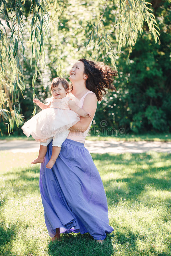 Lifestyle group portrait of smiling white Caucasian brunette mother holding hugging daughter in pink dress dancing stock photos