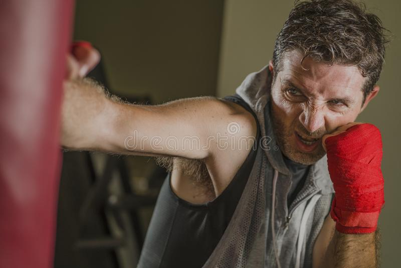 Lifestyle gym portrait of young attractive and fierce looking man training boxing at fitness club doing heavy bag punching workout stock photos