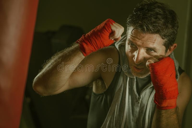 Lifestyle gym portrait of young attractive and fierce looking man training boxing at fitness club doing heavy bag punching workout stock images