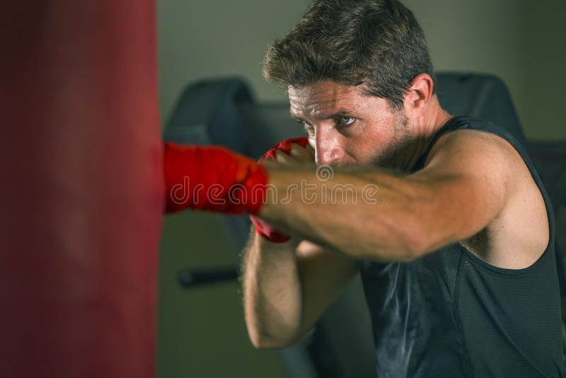 Lifestyle gym portrait of young attractive and fierce looking man training boxing at fitness club doing heavy bag punching workout. With hands and wrist wraps stock image